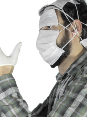 man is freaked out of coronavirus, face is completely covered with epidemic face mask, wearing latex surgical gloves